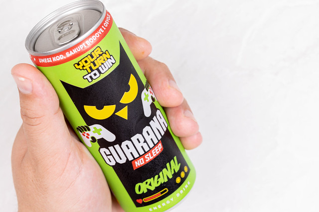 Guarana can in the hand above white background