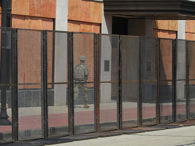Man in military fatigues and armor behind the law enforcement buildings permiter