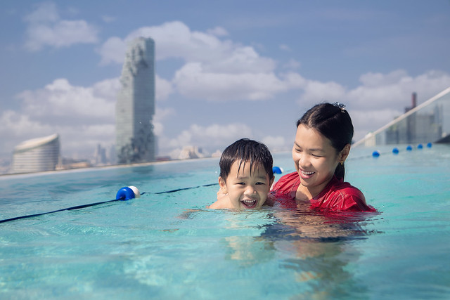 Asian Mother and baby swim in the roof top pool