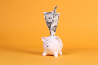 Piggy bank with dollar banknotes on orange background | by wuestenigel