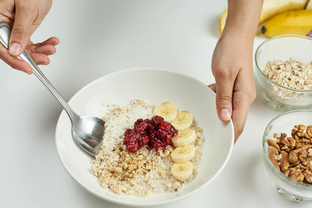 Woman eating healthy breakfast with oats, raspberries and banana slices
