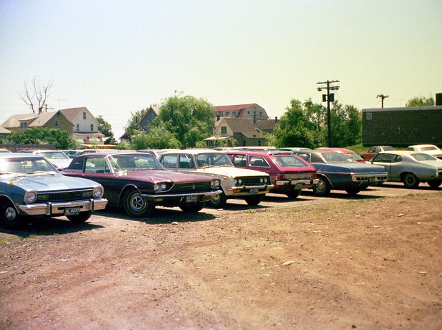 Hot summer day with lots of colorful 1960s and 1970s cars parked at the Surf Club lot. You could tell it was a hot day by the overflow parking on the right. The old abandoned 1890s Sauter Hotel hovers across Merwin Avenue. Milford, Connecticut. July 1974.