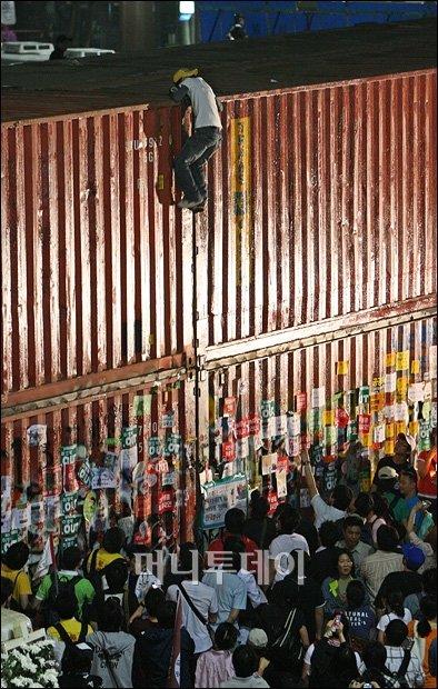 一名韓國抗爭者在2008年反美牛示威中徒手爬上貨櫃,被封為「光化門蜘蛛人」。(圖片來源:Money Today)