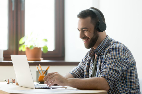 Man with headphones smiling as he works on laptop