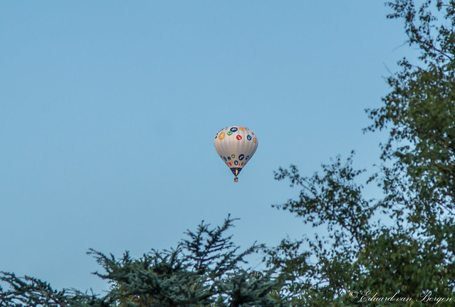 A descending hot air balloon, floating over our house today in the process of landing, 54min. before local sunset.