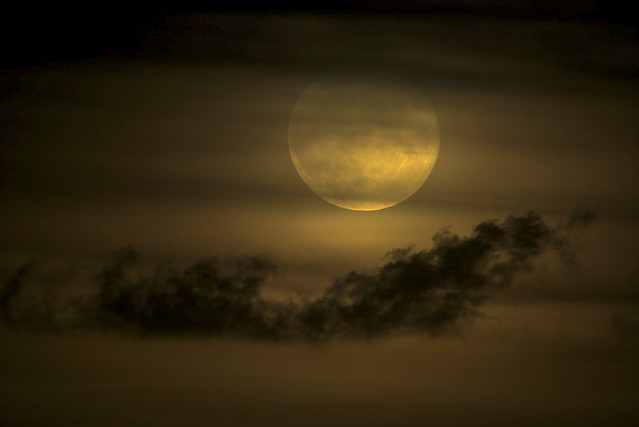 Sept Full Moon Rising; seen at 1000mm rising up over the horizon through the clouds.