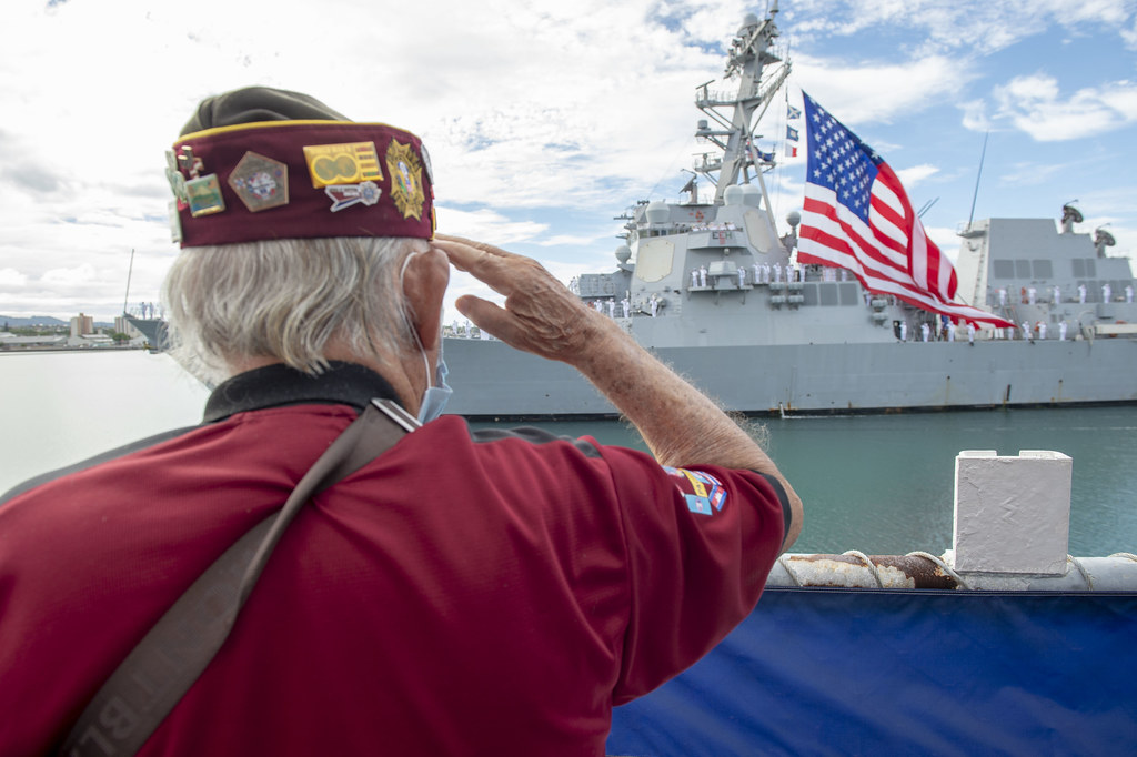 A veteran salutes the national ensign aboard USS Michael Murphy during the 75th anniversary of the End of World War II commemoration ceremony.