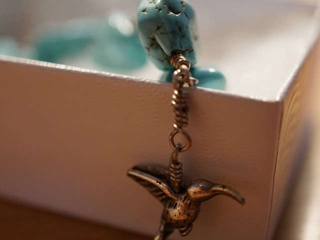 a bracelet of turquoise beads with a silver kingfisher