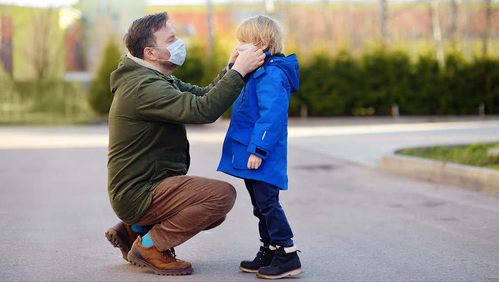 Man putting face covering on child.