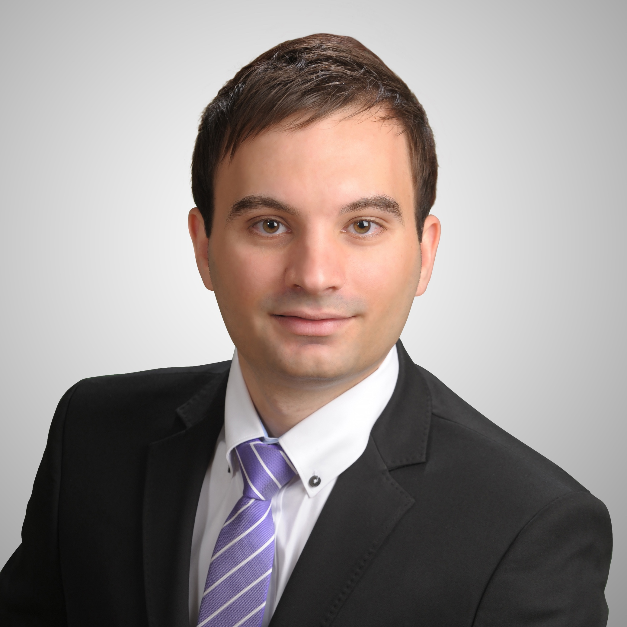 Portrait photograph of Dr Christopher Amaral wearing a black blazer, white shirt and purple and white striped tie in front of a light grey studio background.