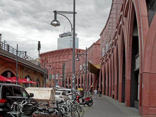 Blick in die gebogene Dircksenstraße in berlin; links die S-Bahn-Trasse, rechts die rote Fassade des Einkaufszentrums ALEXA