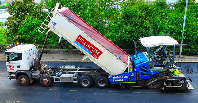Scotland Greenock a lorry tipping tar into a tar laying machine 3 September 2020 by Anne MacKay
