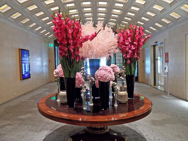 Auf einem großen runden Tisch stehen viele hohe Blumenvasen, darin üppige Sträuße von Gladiolen und Hortensien in verschiedenen Rosatönen