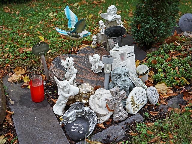 Ein Urnengrab, das bedeckt ist mit unzähligen kleinen Engelfiguren und Steinen mit Sprüchen