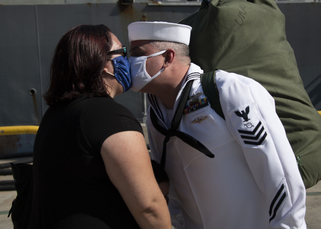Operations Specialist 1st Class Andrew Eischenkisses his wife after USS Rafael Peralta (DDG 115) returns from deployment.