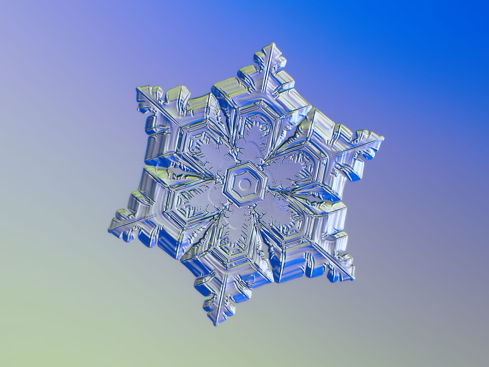 Snowflake photograph: star plate with short, sharp arms and jagged edges, glittering on smooth gradient background