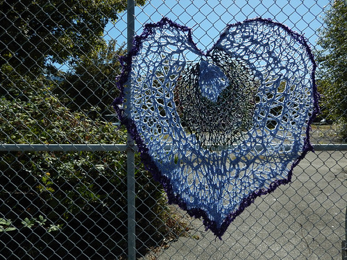 Yarn bombing on a chainlink fence with a crocheted heart