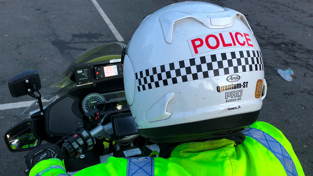 The back of a motorcycle policeman's head and jammer dectector on the dashboard of the bike.