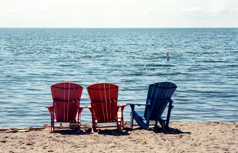 Three Empty Chairs by the Water