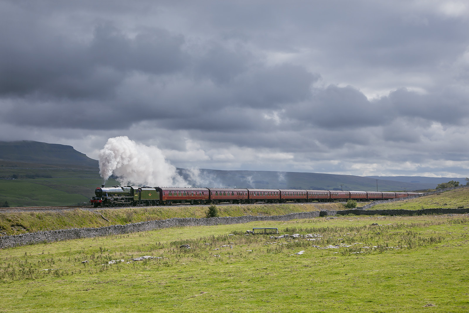 The end of 'the long drag' from Settle Junction to Blea Moor is in sight for driver Chris Cubitt as Jubilee No.45699 'Galatea', masquerading as 45562 'Alberta' forges north with the down Waverley past Selside Shaw during a dramatic burst of sunshine.
