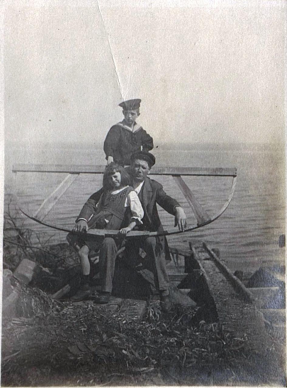 Мужчина с мальчиком и девочкой на берегу широкой реки