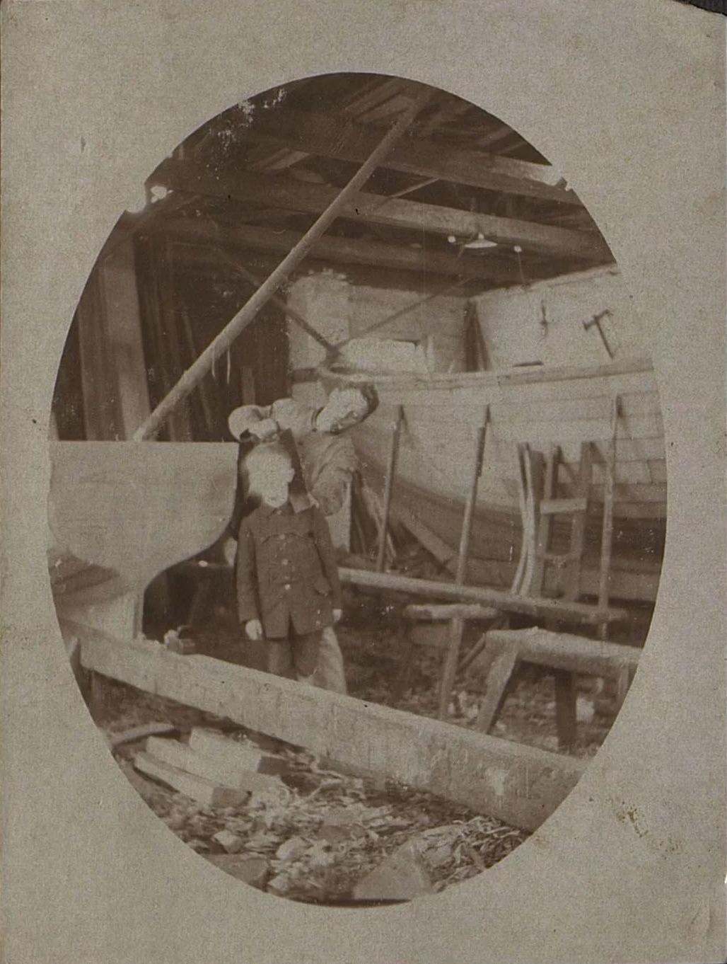 Мужчина и мальчик в помещении, где строят лодки