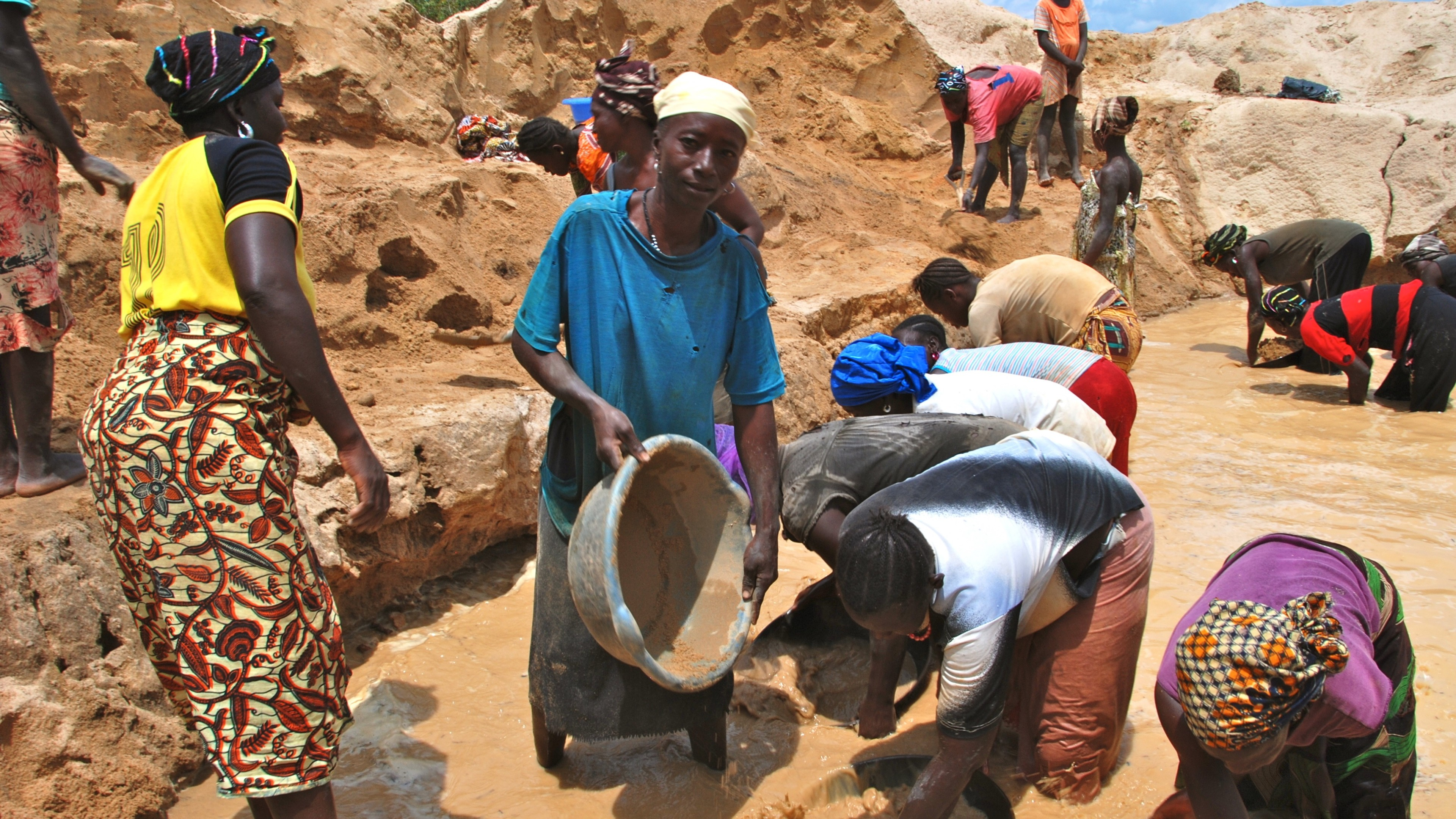 a group of people mining for gold in a clay pool