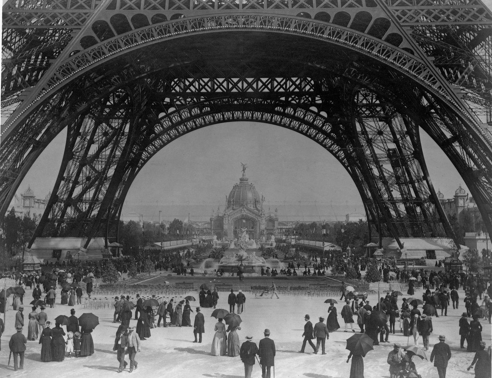 19. Посетители парижской выставки 1889 года прогуливаются по набережной вокруг Эйфелевой башни.