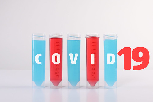 Test tubes with samples and Covid-19 text on white background | by focusonmore.com