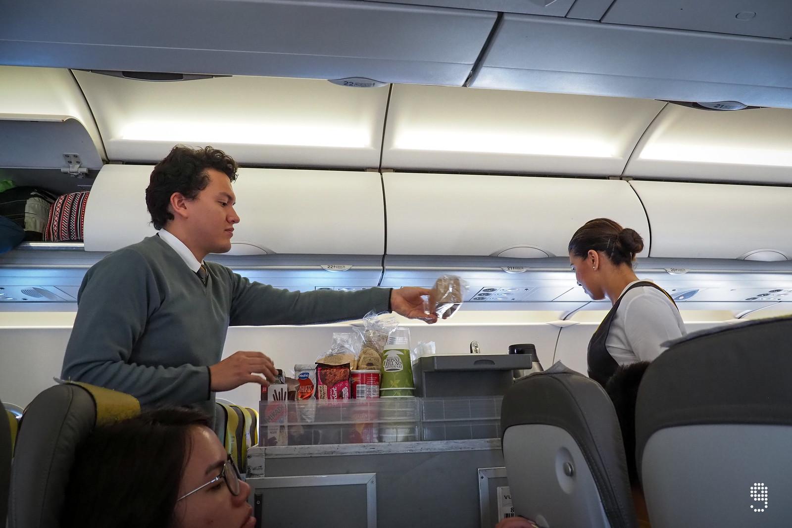 航班上空服人員忙著提供簡單的輕食給乘客