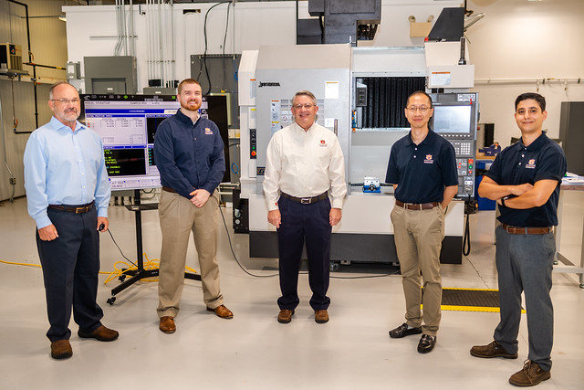 Lewis Payton, Greg Purdy, Greg Harris, Peter Liu and Konstantinos Mykoniatis stand in the Interdisciplinary Center for Additive Manufacturing at Auburn University