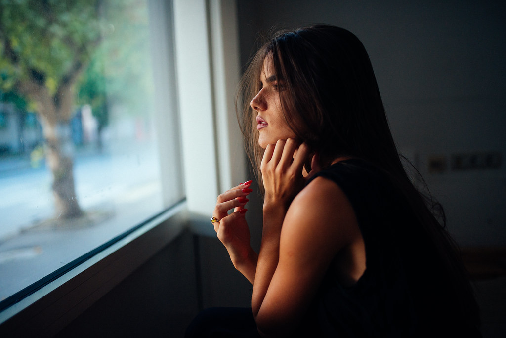A young woman looks out her window.