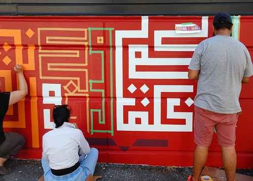 Geometric mural in process, with the artists busy taping and painting, seen on a walk around Main St. to check out the street art from the Vancouver 2018 Mural Fest