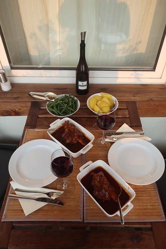In Tomatensoße gegarte Lammkeule mit Salzkartoffeln und grünen Bohnen (Tischbild)