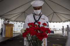 Operations Specialist 2nd Class Jalen Houseworth places a carnation in a vase during a 9/11 remembrance ceremony aboard USS Somerset (LPD 25). (U.S. Navy/MC2 Heath Zeigler)