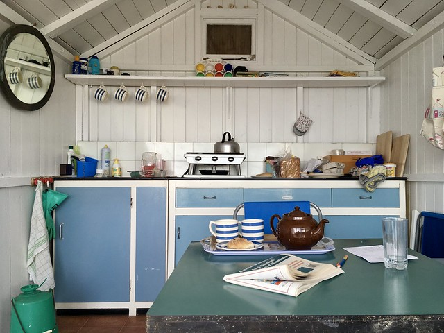 Photo of the interior of a beach hut, with white wooden walls and old blue cupboards