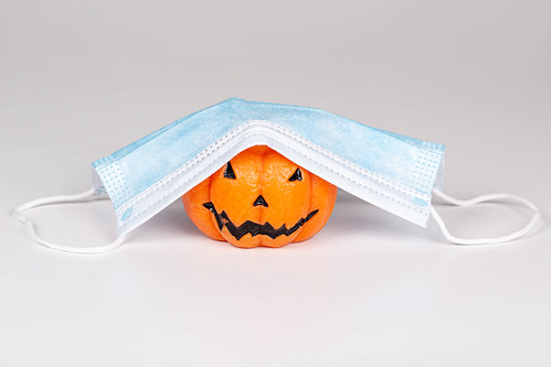 Concept Halloween , COVID-19 prevention. Pumpkin candle with medical mask | by wuestenigel