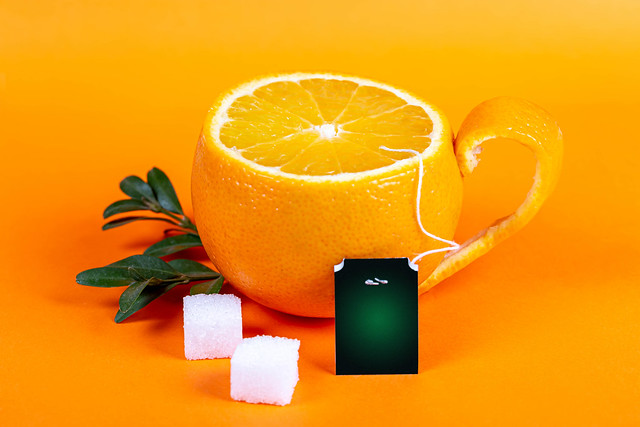 Cup of tea in the form of orange on orange background