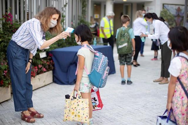 Una trabajadora toma la temperatura a una niña a la entrada del colegio privado internacional American School of Barcelona, situado en Esplugues de Llobregat (Barcelona) EFE
