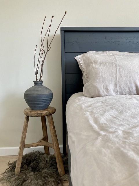 Linnen beddengoed houten kruk kruik vachtje slaapkamer