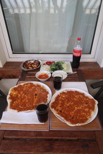 """Lahmacun mit Geflügel-Döner, Salat, Joghurtsoße und """"scharf"""" (Tisch mit zugehörigen Bestandteilen)"""