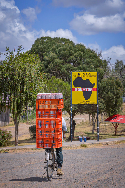 Bicyclist loaded with fresh bread approaching the Equator sign in Nanyuki, Kenya, East Africa