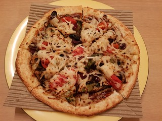 Pizza with BBQ base, cherry tomatoes, basil, pineapple, mushrooms, shiitake mushrooms, olives from Gusto's Gourmet Pizza