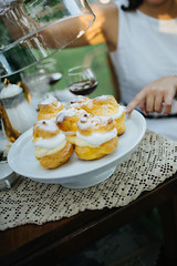Woman lifting the transparent glass lid from the plate full of cream puffs.