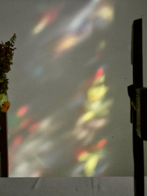 Kirchenfenster beleuchtet die Wand hinter dem Altar