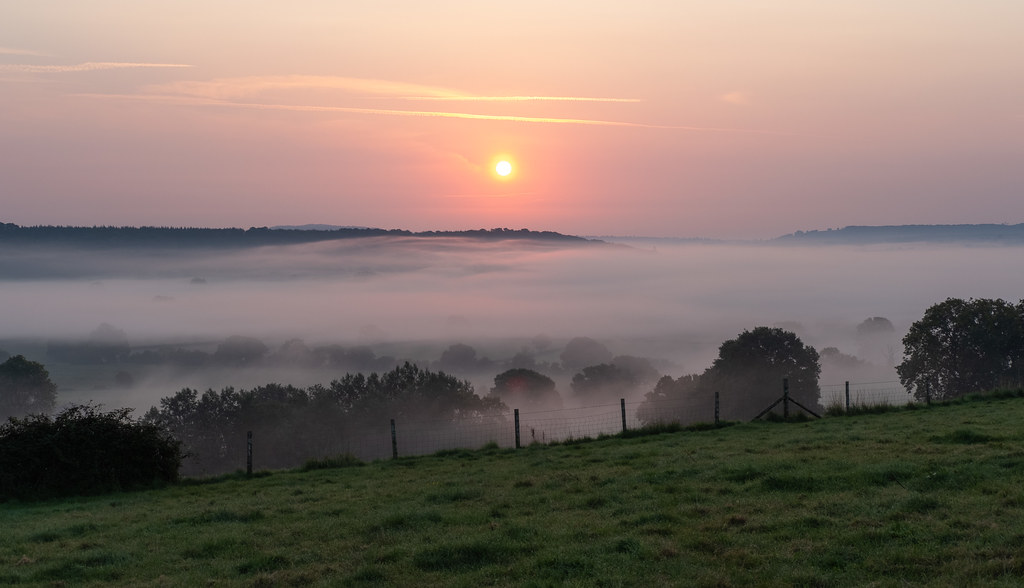 Photo of a valley full of mist with the sun rising above it