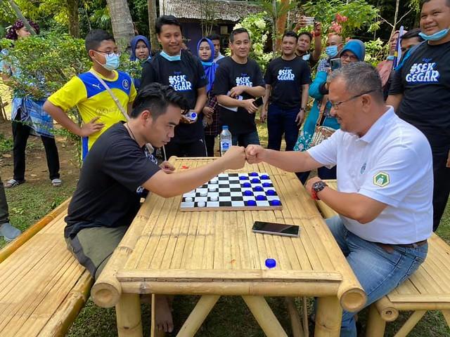 Imej 3_Shah Muhammad  mencuba permainan Dam Aji di Kampung Budaya