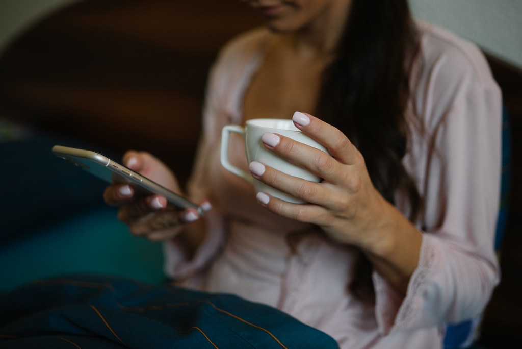 Woman sitting in the bed in the morning, drinking coffee and scrolling through her phone.