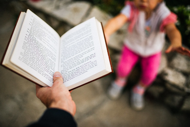 Father handing an open book to his daughter