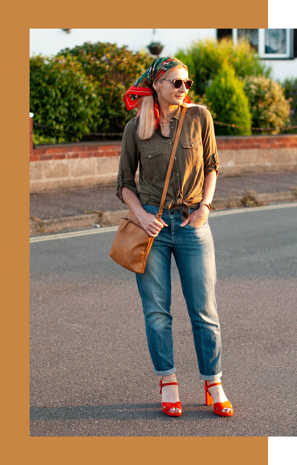 70s Head Scarves and Boyfriend Jeans Older Than Millie Bobby Brown | Not Dressed As Lamb, over 40 style (Catherine is wearing a green and orange patterned headscarf, a loose olive green shirt, boyfriend jeans and strappy orange sandals in a street-style photo)